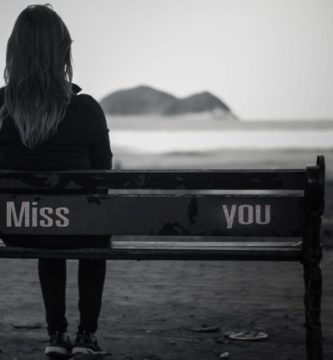 mujer sola sentada en la playa